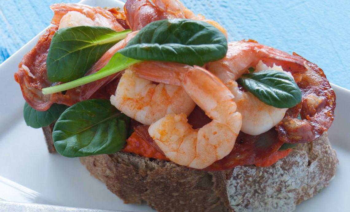 Desembrood met gamba's, chorizo, spinazie en paprika-tapenade